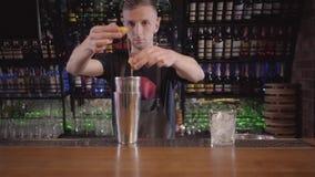 Il barista professionista rompe l'uovo sull'agitatore e separa il bianco dalla fine del tuorlo su La figura dell'uomo è archivi video