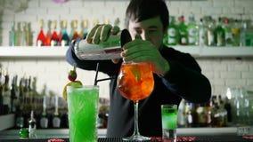 Il barista sparge il ghiaccio dall'agitatore nel cocktail con whiskey ed il limone in bicchiere di vino nel luogo di lavoro nella archivi video