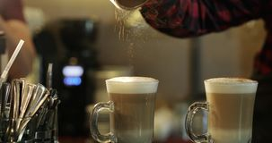 Il barista sparge la cannella in una tazza con latte archivi video