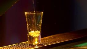 Il barista sta componendo il cocktail ed al bordo del contatore della barra, colpi, fine, luce posteriore, movimento lento stock footage