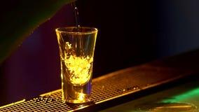 Il barista sta componendo il cocktail ed al bordo del contatore della barra, spruzzata, colpi, fine, luce posteriore, movimento l video d archivio