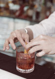 Il barista sta decorando la bevanda con la scorza di limone Immagine Stock Libera da Diritti