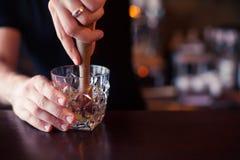 Il barista sta facendo il cocktail al contatore della barra al night-club, tonificato Immagine Stock