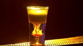 Il barista sta facendo il cocktail e sta aggiungendo il rosso, tre liquidi differenti, al bordo del contatore della barra, fine,  archivi video
