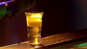 Il barista sta facendo il cocktail e sta aggiungendo il verde, tre liquidi differenti, al bordo del contatore della barra, colpi, stock footage