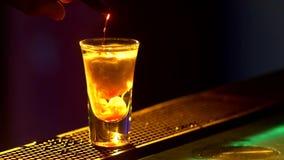 Il barista sta facendo il cocktail e sta aggiungendo il verde, tre liquidi differenti, al bordo del contatore della barra, colpi, video d archivio