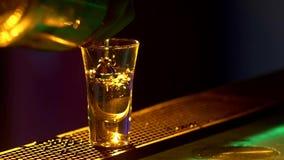 Il barista sta facendo il cocktail e sta aggiungendo l'ingrediente al bordo del contatore della barra, colpi, luce posteriore, mo video d archivio