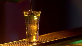 Il barista sta facendo il cocktail e sta aggiungendo tre liquidi differenti, al bordo del contatore della barra, colpi, fine, luc stock footage