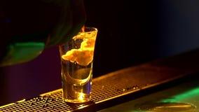Il barista sta facendo il cocktail e sta aggiungendo tre liquidi differenti, al bordo del contatore della barra, colpi, luce post video d archivio