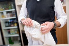 Il barista sta lucidando il vetro, fine su fotografia stock libera da diritti
