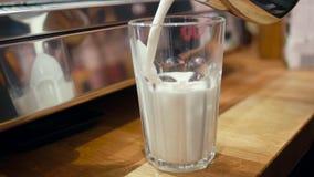 Il barista sta producendo il caffè del latte versando la schiuma del latte ad un vetro nel negozio del caffè video d archivio