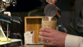 Il barista sta producendo il caffè del latte versando la schiuma del latte ad un vetro nel negozio del caffè archivi video