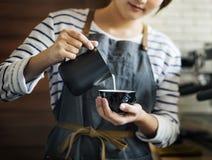 Il barista sta producendo il latte del caffè fotografia stock