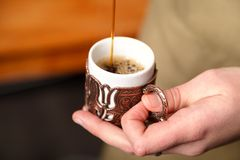 Il barista versa il caffè turco in una tazza impressa tradizionale del rame del metallo, primo piano, fuoco selettivo immagini stock