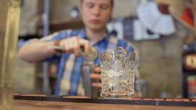 Il barista versa il cocktail in un vetro con ghiaccio stock footage