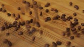 Il barista versa fuori i chicchi di caff? da una borsa su una tavola di legno in una caffetteria archivi video