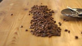 Il barista versa fuori i chicchi di caff? da una borsa su una tavola di legno in una caffetteria video d archivio