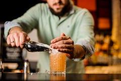 Il barista versa il ghiaccio in un cocktail arancio dell'estate Immagini Stock Libere da Diritti