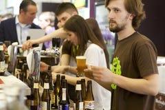 Il barista versa la birra del rubinetto del mestiere in pub occupato Immagini Stock Libere da Diritti