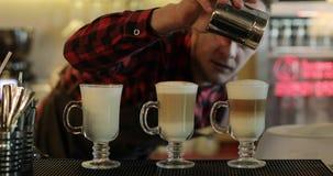 Il barista versa la cannella nelle tazze di caffè fresche video d archivio