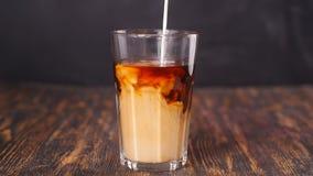 Il barista versa la crema in un cocktail del caffè