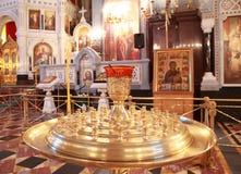 Il basamento per le candele si avvicina all'altare all'interno della cattedrale Fotografie Stock Libere da Diritti