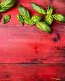 Il basilico fresco va con le gocce di acqua su fondo di legno rosso, il verticale, vista superiore Immagine Stock
