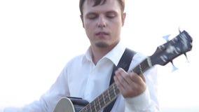 Il bassista gioca una chitarra su un plateau roccioso stock footage