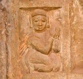 Il bassorilievo di pietra con la donna ha afferrato insieme le sue mani nella preghiera Immagini Stock