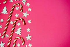 Il bastoncino di zucchero di Natale si è trovato anche nella fila su fondo rosa con il fiocco di neve e la stella decorativi Disp immagini stock