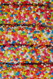 Il bastone variopinto del biscotto ha ricoperto il fondo di struttura dello zucchero dell'arcobaleno dello smalto illustrazione di stock