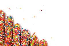 Il bastone variopinto del biscotto ha ricoperto lo zucchero dell'arcobaleno dello smalto di fondo bianco dello spazio illustrazione di stock