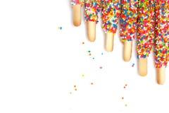 Il bastone variopinto del biscotto ha ricoperto lo zucchero dell'arcobaleno dello smalto di fondo bianco dello spazio illustrazione vettoriale