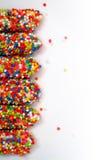 Il bastone variopinto del biscotto ha ricoperto lo zucchero dell'arcobaleno dello smalto di fondo bianco dello spazio royalty illustrazione gratis