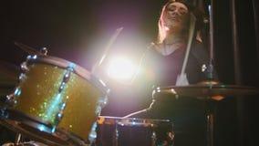 Il batterista gotico della percussione della ragazza esegue la musica suddivide - la banda rock che prova nel garage Fotografia Stock