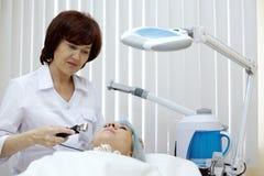 Il Beautician elabora la pelle del fronte del paziente Immagini Stock Libere da Diritti