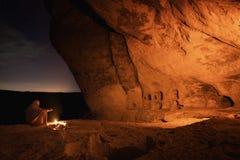 Il beduino nella caverna della Crimea Kachi-Kalyon è riscaldato dal fuoco sui precedenti del cielo stellato fotografia stock libera da diritti