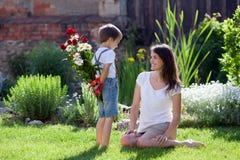 Il bei bambino e mamma in primavera parcheggiano, fioriscono e presentano madre Fotografie Stock Libere da Diritti