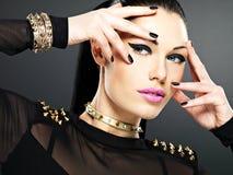 Il bei fronte della donna di modo con i chiodi neri e luminosi fanno Immagine Stock