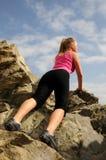 Il bello alpinista della donna sta arrampicandosi su una montagna Immagine Stock Libera da Diritti