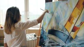 Il bello artista della ragazza è occupato vista sul mare dipingere su tela facendo uso della tavolozza, della spazzola e della te stock footage