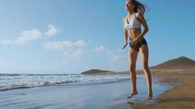 Il bello atleta della ragazza con i bei seni negli shorts neri ed in una cima bianca si accovaccia e compone un salto circolare video d archivio