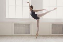 Il bello ballerine sta nella posizione di balletto di arabesque Immagini Stock