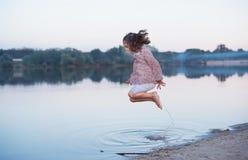 Il bello bambino con capelli ricci allegramente salta sulla banca del lago Passeggiata attiva della molla all'aperto fotografia stock libera da diritti