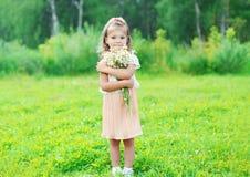 Il bello bambino della bambina con le camomille del mazzo fiorisce di estate Fotografia Stock Libera da Diritti