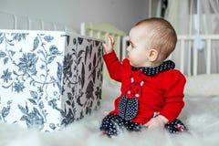 Il bello bambino si siede e tira i giocattoli dalla scatola bedroom Il raggiro fotografia stock libera da diritti