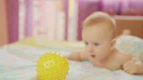 Il bello bambino sta trovandosi Tira la sua mano verso la palla, vuole giocare con  video d archivio