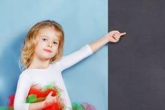 Il bello bambino sveglio ha posato Una bambina con i punti dei capelli biondi il suo dito ad uno spazio su un fondo nero fotografie stock
