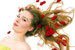 Il bello blonde in petali Immagine Stock