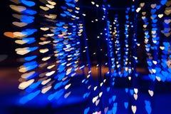 Il bello bokeh fatto del blu caldo ha offuscato le luci sotto forma di cuori Immagini Stock